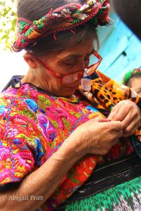 A woman looking at her own huipil